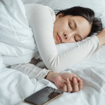 Dame sover i seng med dyne og pude